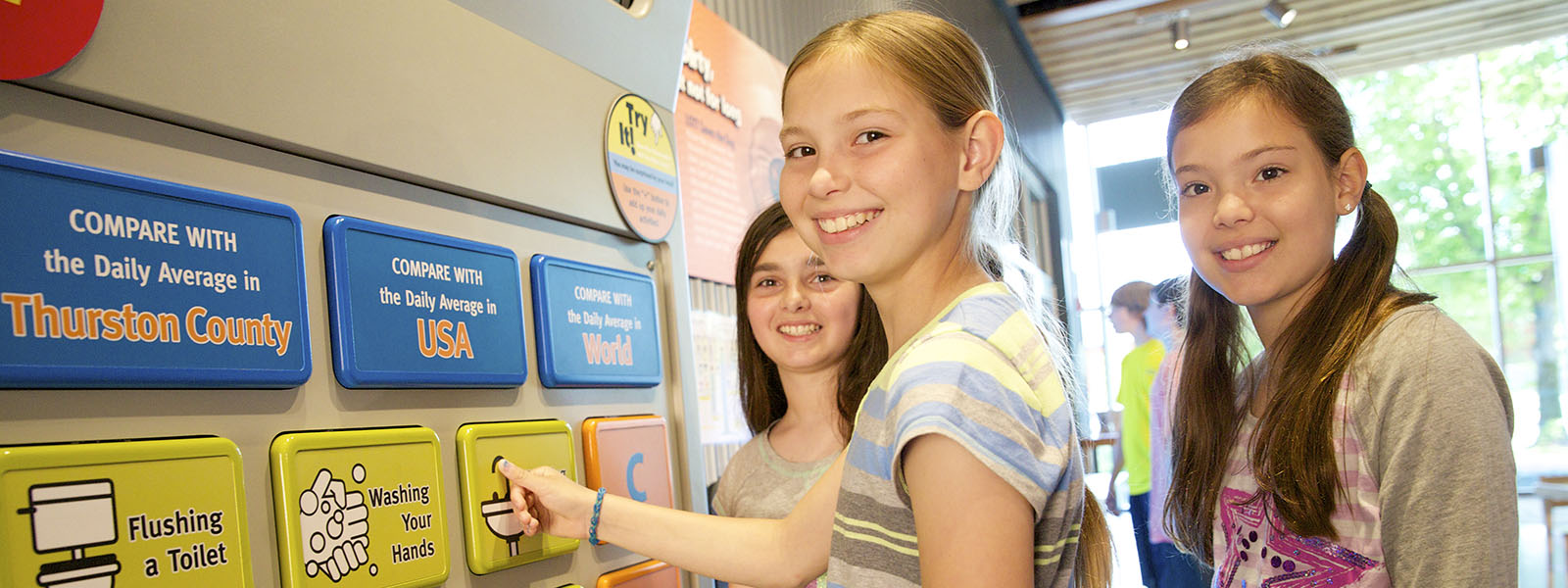 Image of three girls learning at a kiosk in the WET Science Center